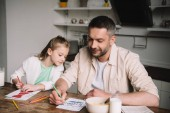 Fotografie happy dad with adorable daughter drawing fathers day greeting cards while sitting at kitchen table with served breakfast