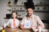 happy dad with adorable daughter showing fathers day greeting cards while sitting at wooden table with served breakfast
