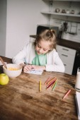 adorable child drawing fathers day greeting card while sitting at wooden table