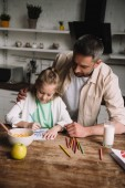 Fotografie happy father hugging adorable daughter sitting at kitchen table with served breakfast and drawing fathers day greeting card