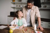 happy father hugging adorable daughter sitting at wooden table with served breakfast and drawing fathers day greeting card
