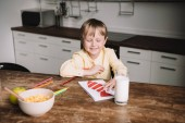 Fotografie cute boy sitting at wooden table near served breakfast and drawing fathers day greeting card