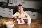cheerful boy smiling at camera while sitting at wooden table and drawing fathers day greeting card