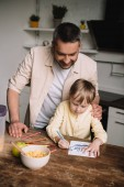 happy father hugging adorable son sitting at kitchen table and drawing fathers day greeting card