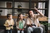kyiv, ukraine - 10. Mai 2019: glückliche Familie spielt Videospiel mit Steuerknüppeln, während Vater Siegergeste zeigt.