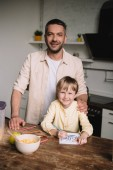 Fotografie happy father hugging adorable son sitting at kitchen table and drawing fathers day greeting card