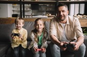 KYIV, UKRAINE - MAY 10, 2019: Happy father and adorable kids playing video game with joysticks at home.