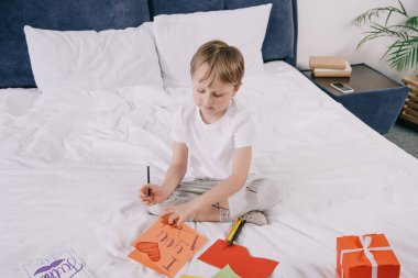 cute boy making fathers day greeting card with i love you dad inscription and heart symbol while sitting on bedding near gift box