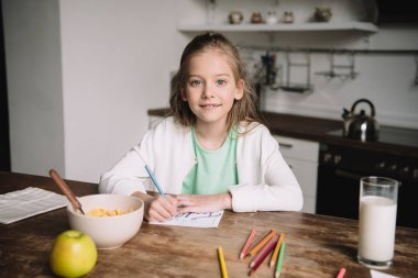 cute child smiling at camera while sitting at kitchen table and drawing fathers day greeting card