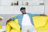 high angle view of african american man sitting on couch in vr headset