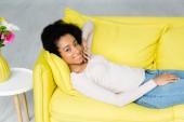 nagy látószögű nézet afro-amerikai nő feküdt a kanapén, és néztem kamera