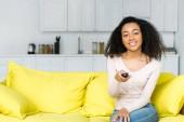 Veselá africká americká žena držící dálkový ovládače v ruce a dívá se na kameru