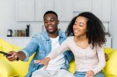 Afroameričan, který drží dálkový ovladač v ruce a tráví víkend s přítelkyní