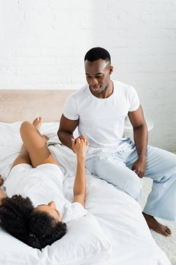 african american man sitting on bed, looking at beautiful girlfriend