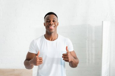 Front view of happy african american man showing thumbs up, looking at camera stock vector