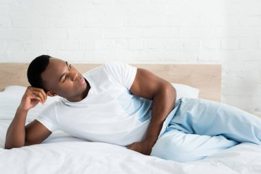 Calm african american man looking away, laying on bed in white room stock vector