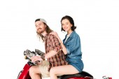 side view of girl and young man looking at camera and smiling, sitting on red scooter isolated on white