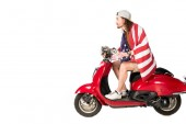 side view of young man with flag of America sitting on red scooter isolated on white