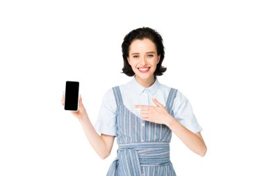 beautiful girl pointing with finger at smartphone and smiling isolated on white