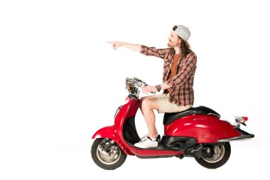side view of young man sitting on red scooter and pointing with finger isolated on white