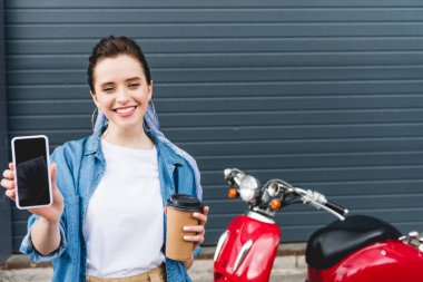front view of beautiful girl standing near red scooter, holding paper cup with coffee and smartphone