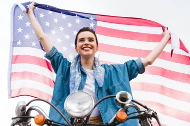 low angle view of beautiful girl sitting on scooter, holding American flag and smiling on sky background