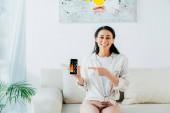 Veselá Latinská žena se smartphone s grafy a grafy na obrazovce