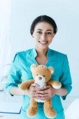 pretty latin doctor holding teddy bear while smiling at camera
