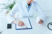 levágott lövés a fiatal orvos írásban a vágólapra ülve a munkahelyen és a gazdaság tabletták konténer