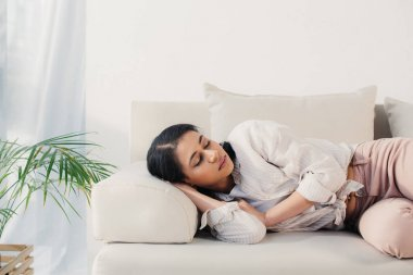 beautiful tired latin woman lying with closed eyes on sofa at home