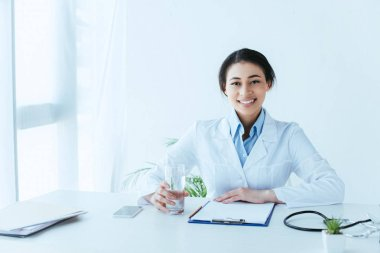 Attractive latin doctor smiling at camera while sitting at workplace with glass of water stock vector