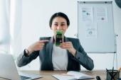 mladá latinská podnikatelka ukazující prstem na smartphone s rezervační aplikací na obrazovce