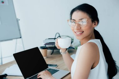 Cheerful latin businesswoman holding coffee cup and using laptop while smiling at camera stock vector