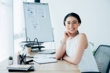 Cheerful latin businesswoman in glasses smiling at camera while sitting at workplace in office stock vector