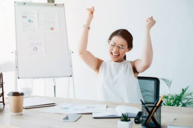 excited businesswoman celebrating triumph while sitting at workplace in office