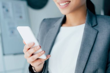 Cropped shot of smiling latin businesswoman using smartphone in office stock vector
