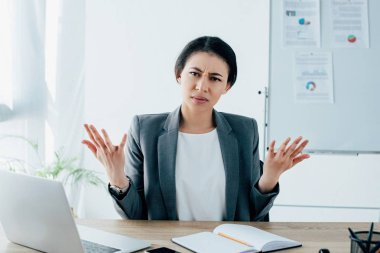 displeased latin businesswoman gesturing while sitting at workplace and looking at camera