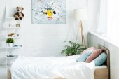 bed with white bedding, blue and pink pillows near rack and painting