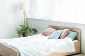 bed with white bedding, blue and pink pillows near floor lamp and plant