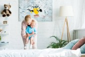 attractive mother holding in arms cute toddler son in bedroom