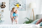 attraktive Mutter hält in den Armen niedlichen Kleinkind Sohn im Schlafzimmer
