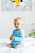 cute toddler boy sitting on bed with white bedding at home