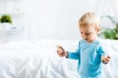 rozkošný batole, stojící s dřevěnými hračkami v domácnosti u postele