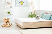 bed with white bedding near teddy bear and wooden rocking horse in bedroom