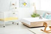 Baby-Krippe in der Nähe von Bett mit weißen Bettwäsche und Kissen in der Nähe von Teddybär und Schaukelpferd