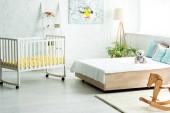 Baby-Krippe in der Nähe von Bett mit weißen Bettwäsche und Kissen in der Nähe von Teddybär und Holz Schaukelpferd