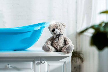 Selective focus of teddy bear near blue baby bathtub in bathroom stock vector