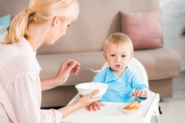 selective focus of blonde mother holding bowl and feeding cute toddler son at home