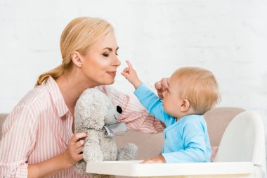 cute toddler son pointing with finger at cheerful mother with teddy bear