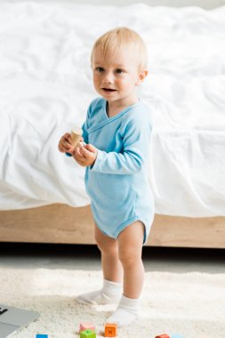 smiling toddler kid standing with wooden toy near bed